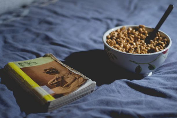 Someone heading to bed with a good book and a bowl of cereal